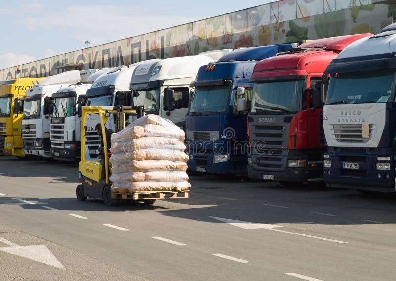 有货物的电铲车在卡车长的系列的背景站立在卸载的在仓库 库存图片