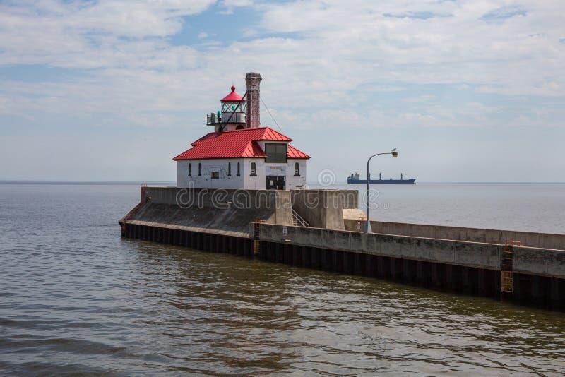有货船通过的红色屋顶灯塔 库存照片