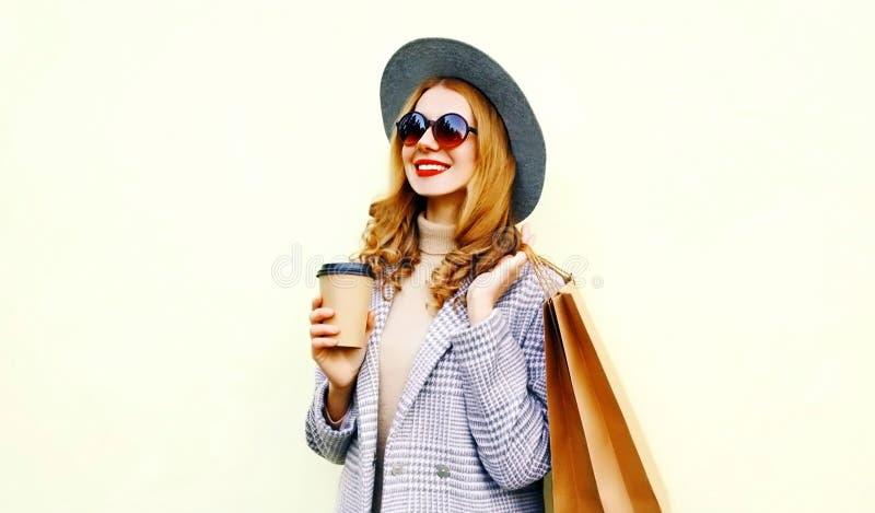 有购物带来和咖啡杯的,佩带的桃红色外套,在背景的圆的帽子画象微笑的妇女 免版税库存照片
