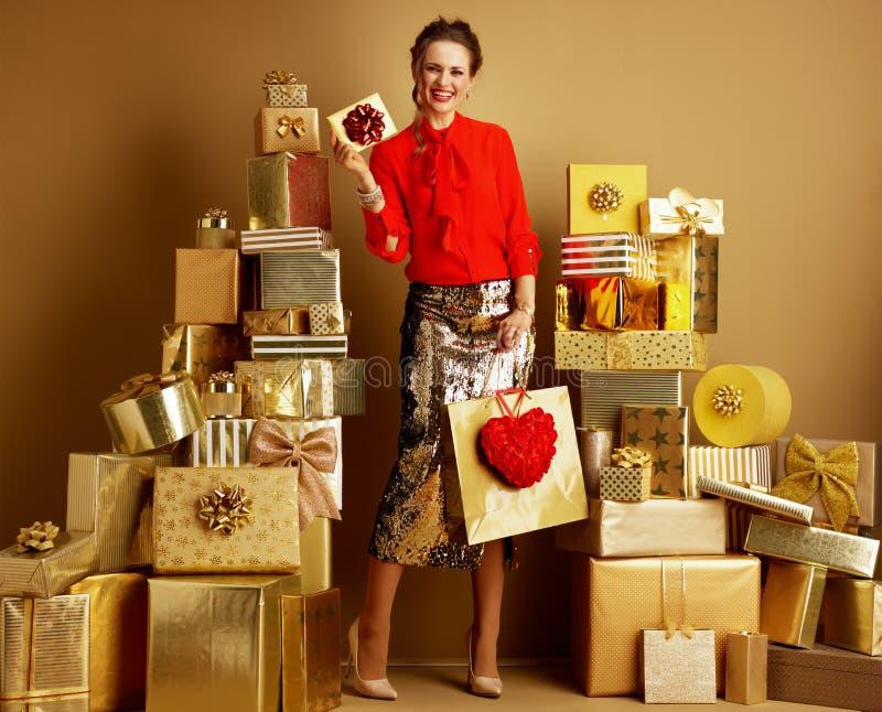 有购物带来和心脏陈列礼品券的时尚商人 免版税图库摄影