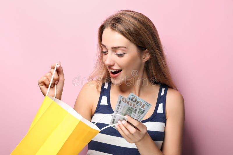 有购物带来和金钱的美女在颜色背景 免版税库存照片