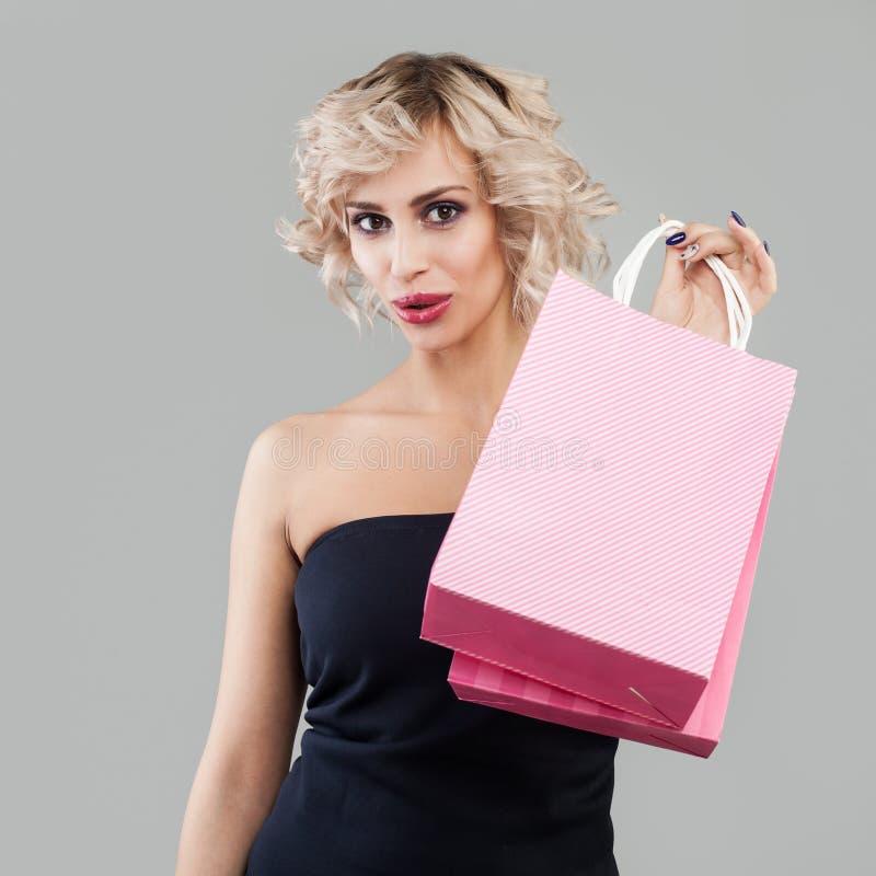 有购物带来的俏丽的惊奇的妇女 免版税库存照片