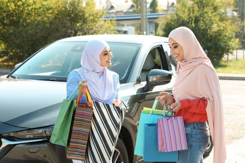 有购物带来的回教妇女在汽车附近 免版税库存图片