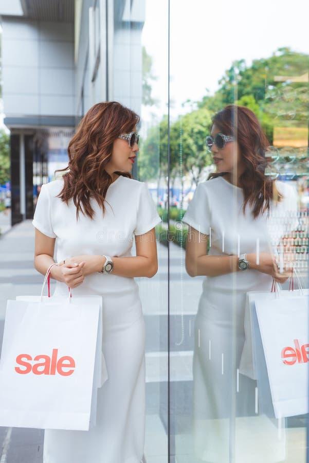 有购物带来的年轻女人在看wi的百货店 免版税图库摄影