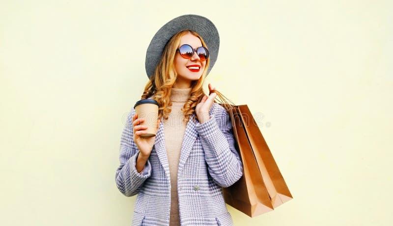 有购物带来的画象微笑的年轻女人,拿着咖啡杯,佩带的桃红色外套,在背景的圆的帽子 库存图片