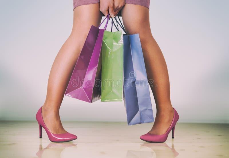 有购物带来的精密妇女腿在她的手上 库存图片