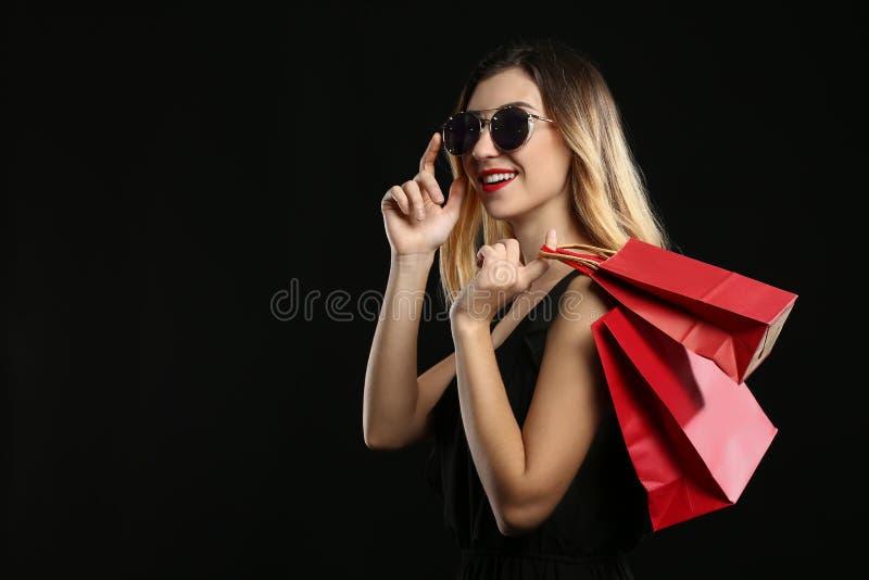 有购物带来的美丽的年轻女人在黑暗的背景 免版税库存图片