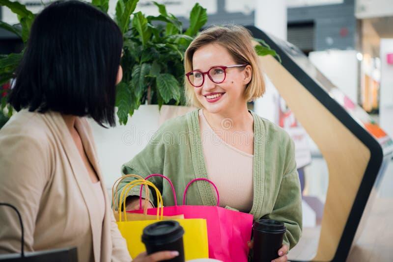 有购物袋和咖啡纸杯的愉快的少妇坐,休息和谈话在购物在购物中心以后 免版税库存照片