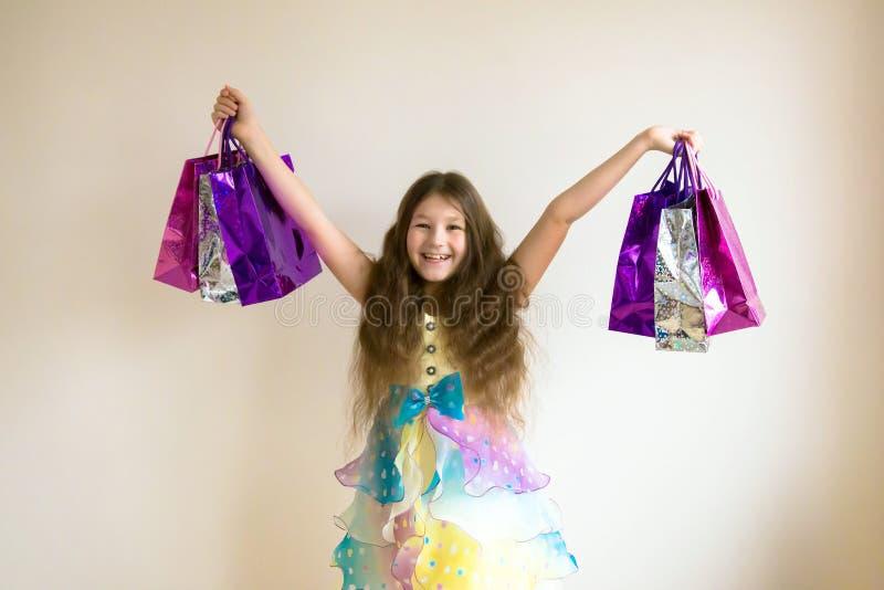 有购物袋和礼物的美丽的微笑的小女孩 免版税库存照片