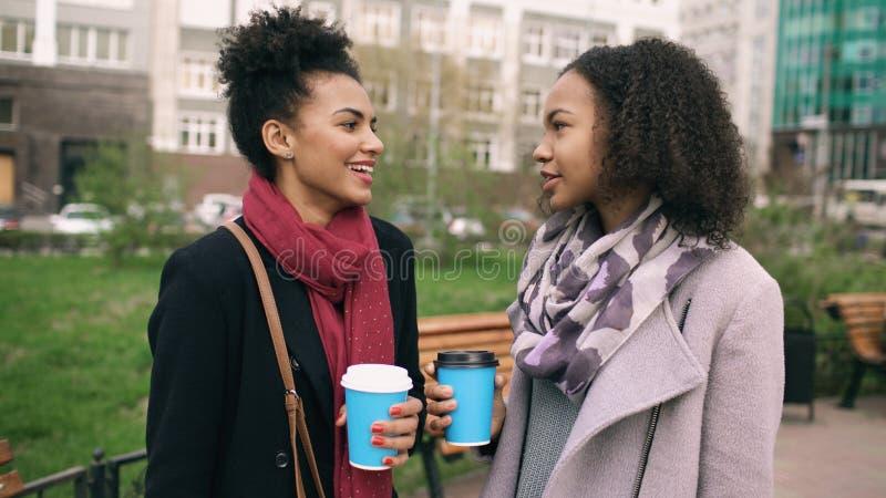 有购物袋的两名可爱的混合的族种妇女喝coffe和谈话在街道 微笑的女孩和 库存照片
