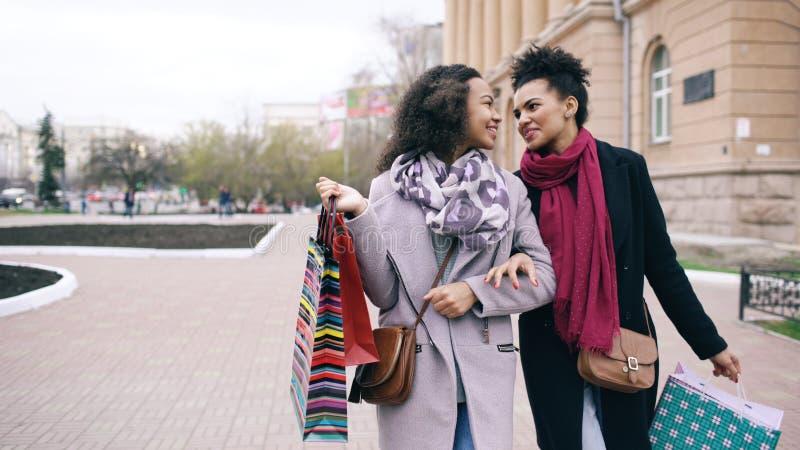 有购物袋的两名可爱的混合的族种妇女谈话和步行沿着向下街道的 女朋友以后获得乐趣 库存照片