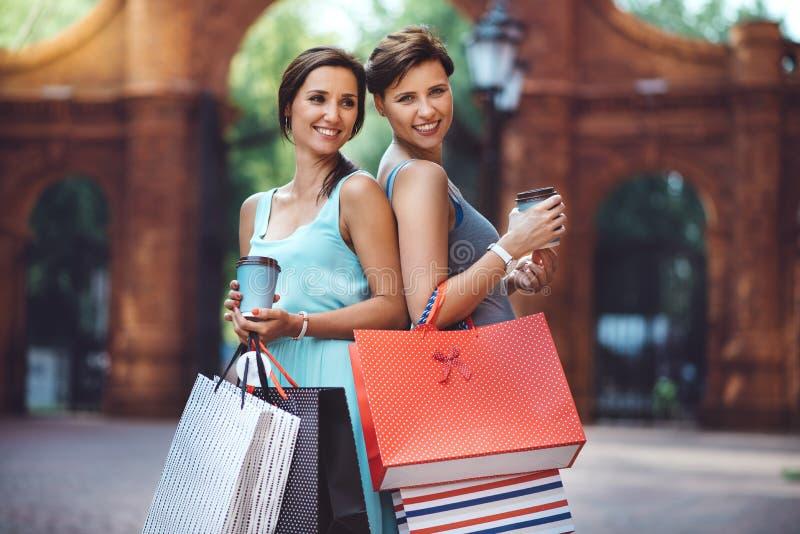 有购物袋的两名年轻时尚妇女在城市 库存图片