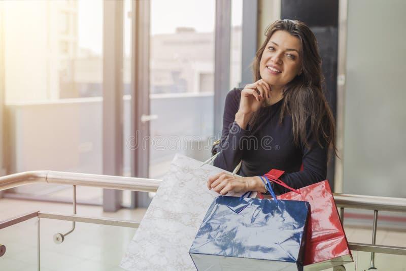 有购物袋的华美的女孩在商城 免版税图库摄影