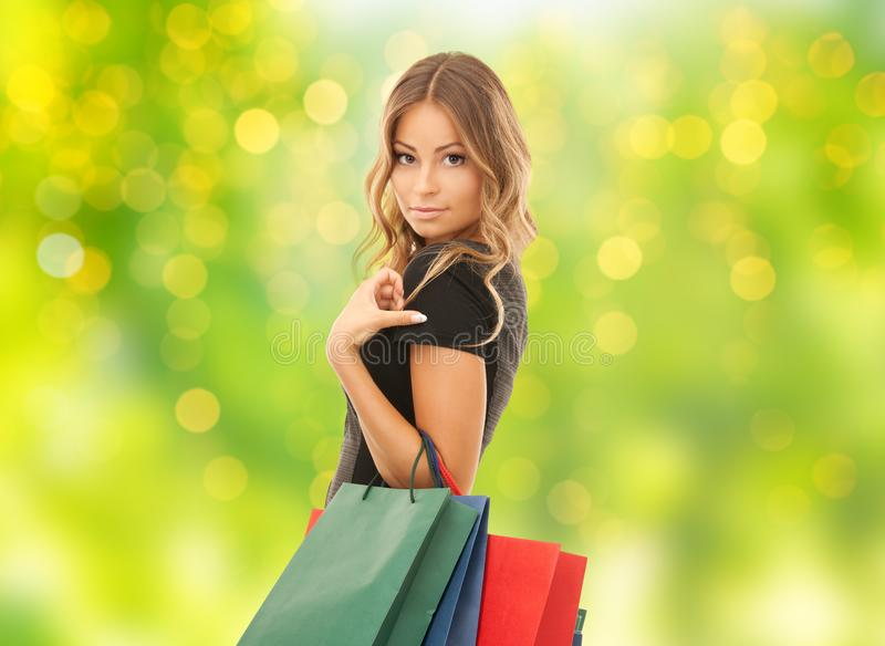 有购物袋的少妇在光 库存图片