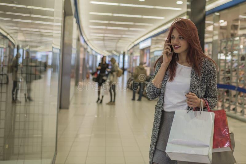 有购物袋的微笑的女孩在商城 免版税库存照片