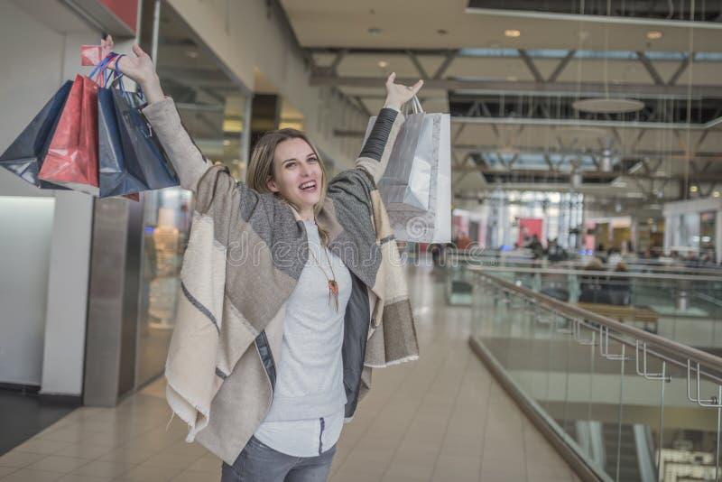 有购物袋的微笑的女孩在商城 免版税库存图片