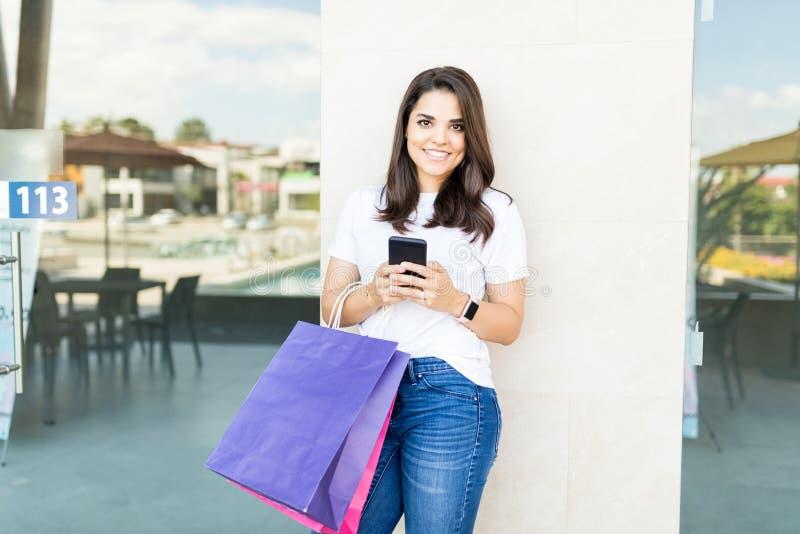 有购物袋的微笑的顾客使用在购物中心的手机 库存图片