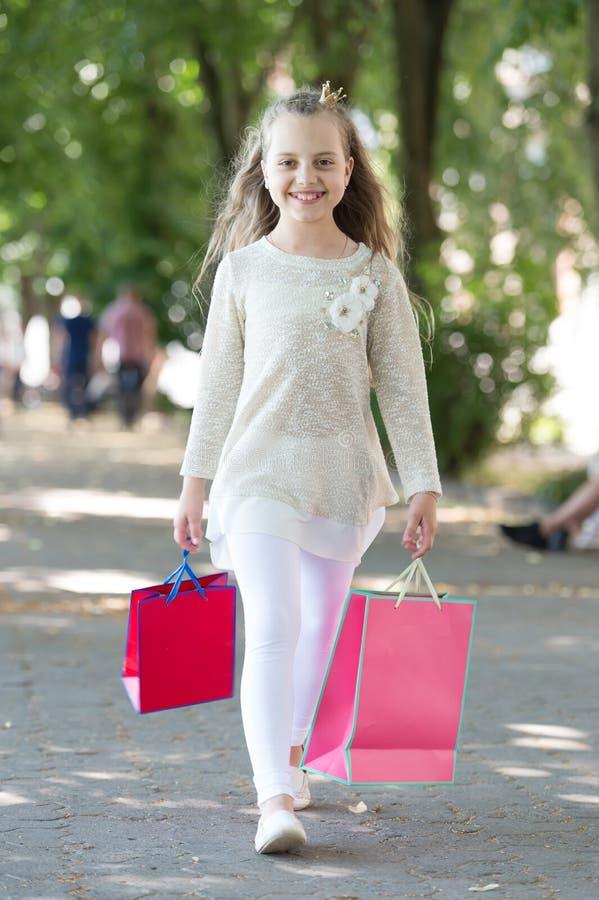有购物袋的愉快的女孩在公园走 孩子顾客微笑以时尚给室外穿衣 有冠的小公主 免版税库存照片