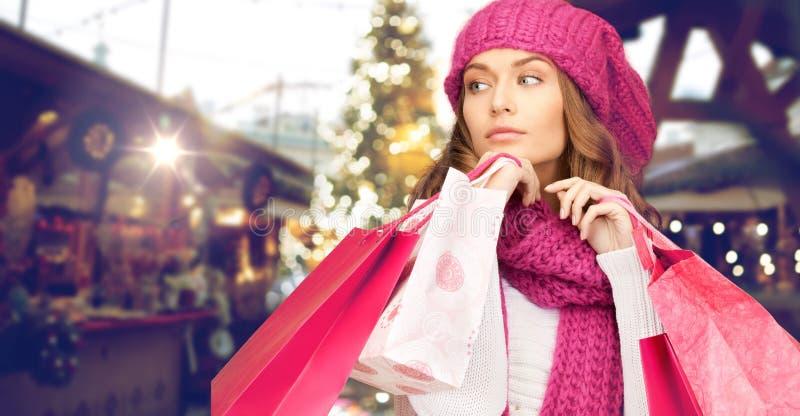 有购物袋的愉快的妇女在公平的圣诞节 免版税库存照片