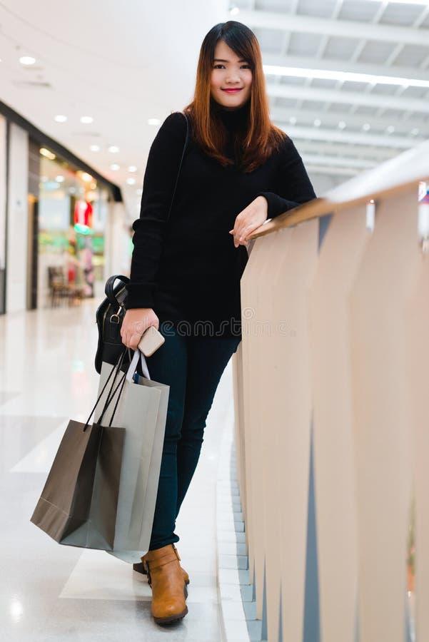 有购物袋的愉快的美丽的妇女在商店站立 有购买的可爱的亚裔妇女在大购物中心请求 库存图片