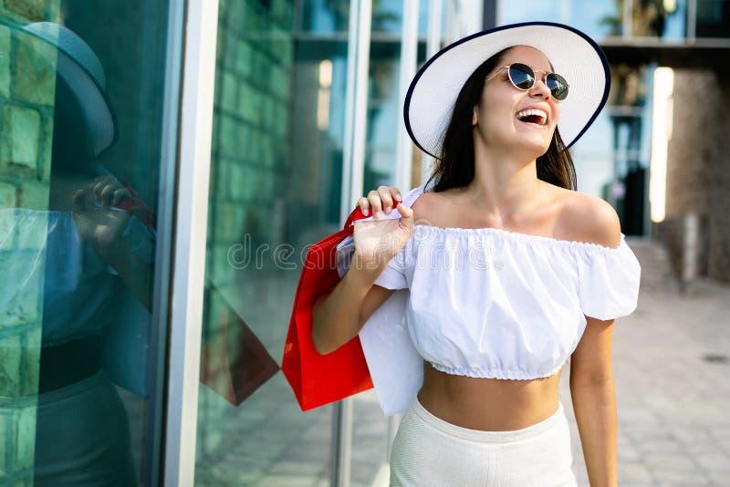 有购物袋的美丽的妇女在ctiy 销售、购物、旅游业和愉快的人概念 库存照片