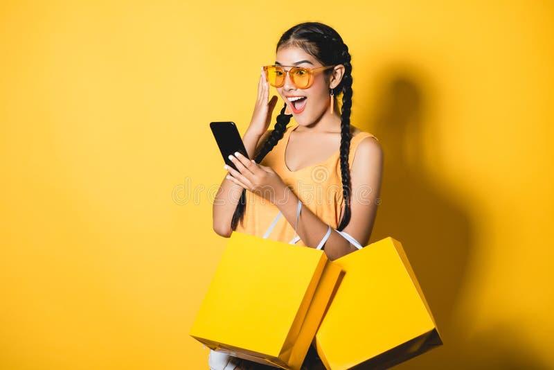 有购物袋的美丽的少妇使用她巧妙的电话 免版税库存照片