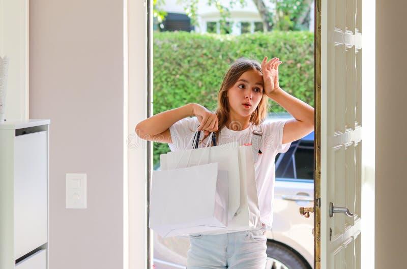 有购物袋的美丽的年轻青春期前的女孩在她手回来的家庭疲乏在购物以后 免版税库存图片