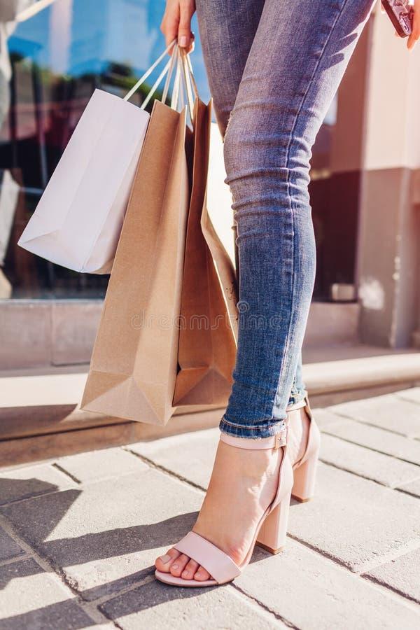 有购物袋的美丽的时髦的少妇走在城市街道上的在夏天 鞋子和购买特写镜头  销售额 免版税库存照片