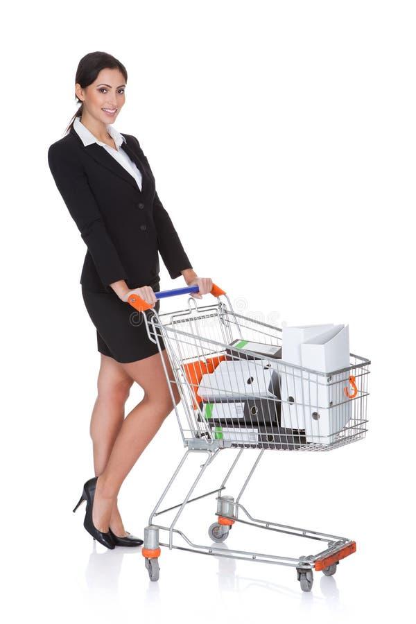 有购物车的可爱的女实业家 免版税库存照片