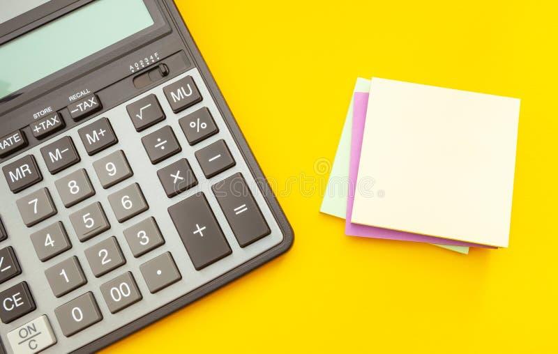 有贴纸的现代计算器关于黄色背景的笔记的,顶视图 免版税图库摄影