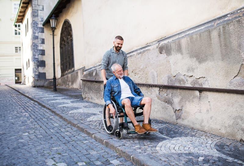 有资深父亲的一个成人儿子在步行的轮椅的在镇里 免版税库存照片