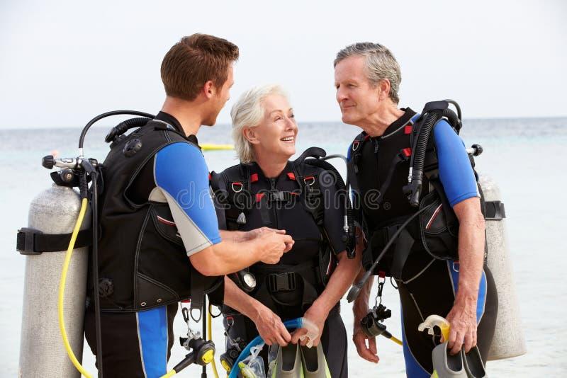 有资深的夫妇与辅导员的佩戴水肺的潜水教训 库存图片