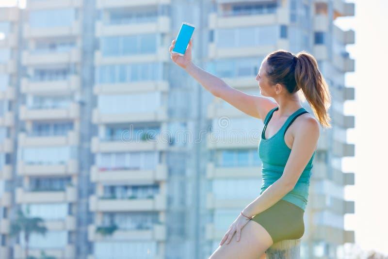有赛跑者的女孩休息射击selfie 免版税库存图片