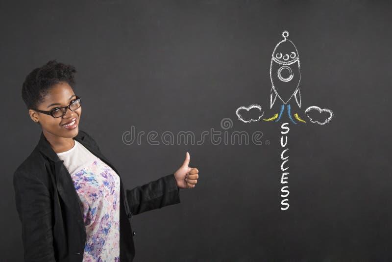 有赞许手势的非洲妇女和成功在黑板背景迅速上升 免版税库存照片
