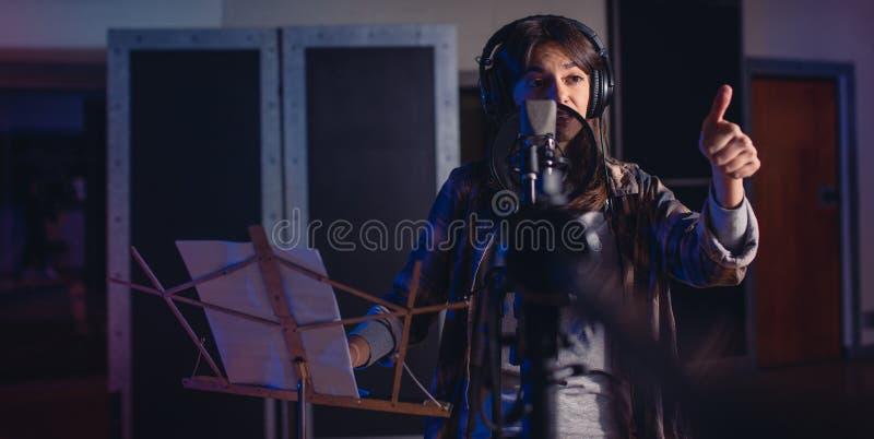 有赞许的女歌手签到录音室 库存图片