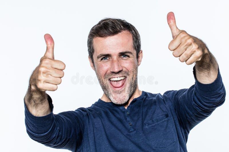 有赞许笑的动态英俊的年轻人,显示喜悦 库存图片