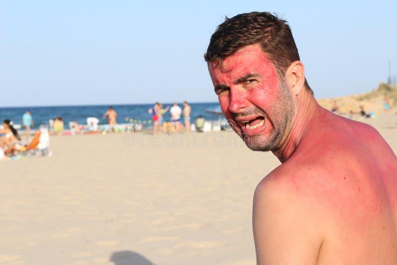 有赤红的人哭泣在海滩的 库存照片