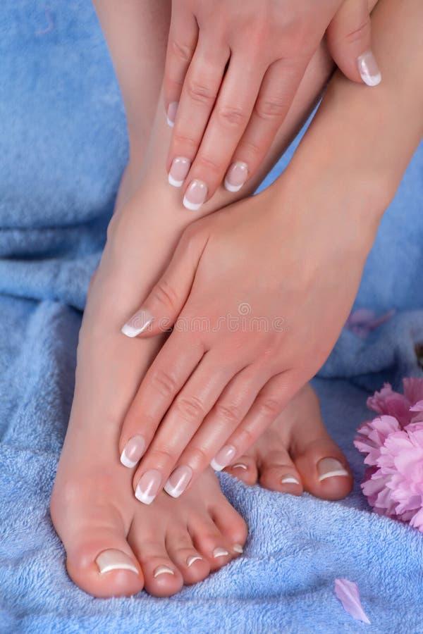 有赤脚和手的女性在蓝色毛巾和装饰桃红色花温泉演播室的腿有法式修剪的和修脚 库存照片