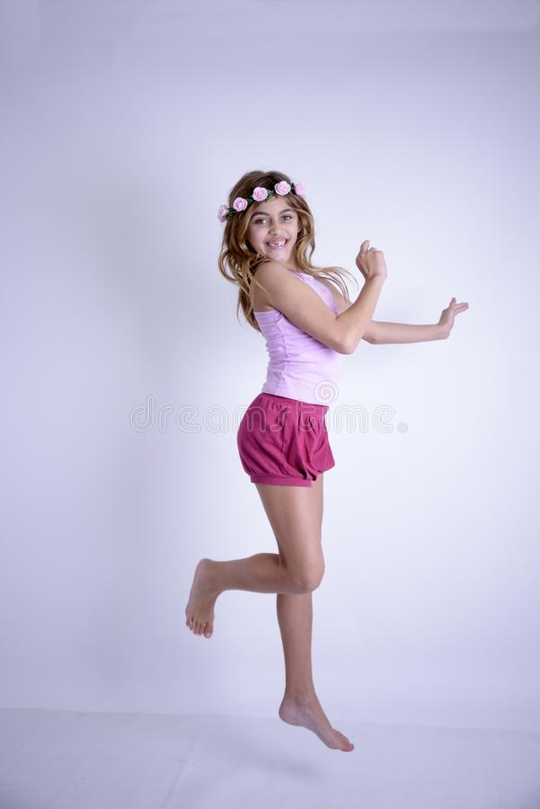 有赤脚和玫瑰的超级愉快的跳跃的女孩在头 库存照片