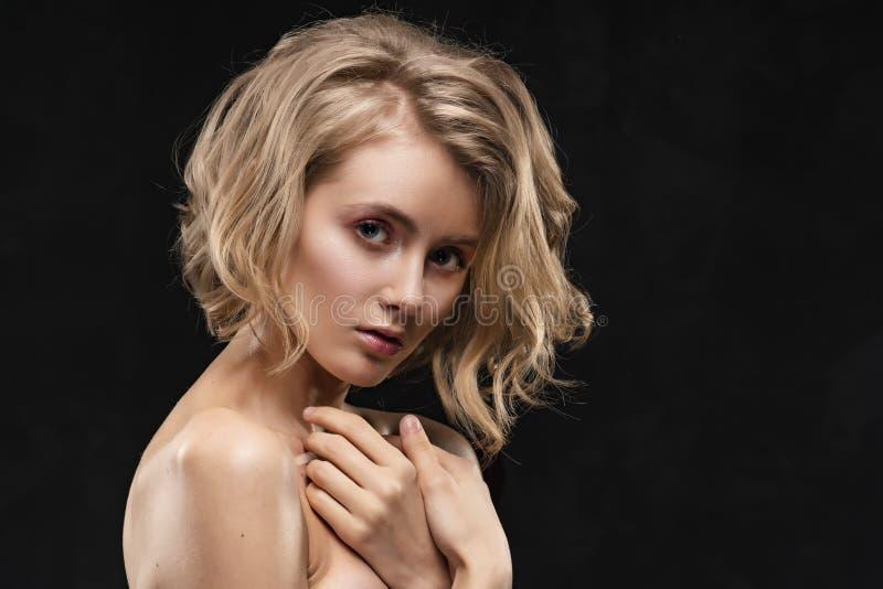 有赤裸肩膀的美丽的年轻白肤金发的女孩和卷发,摆在,用她的手肉欲上按了到她的乳房,在a 免版税库存图片