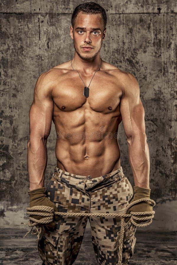 有赤裸身体的坚强的运动人在军用裤子 免版税库存照片