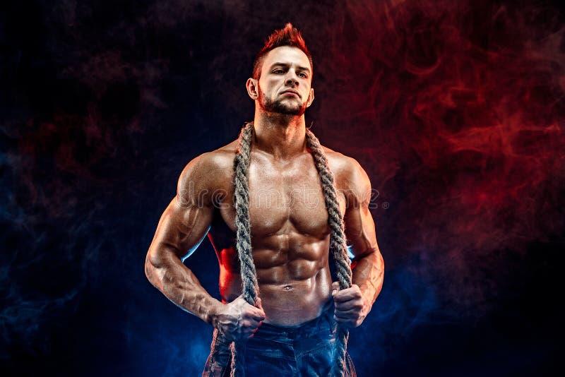 有赤裸身体的坚强的运动在脖子的人在军用裤子和绳索染黑 库存图片