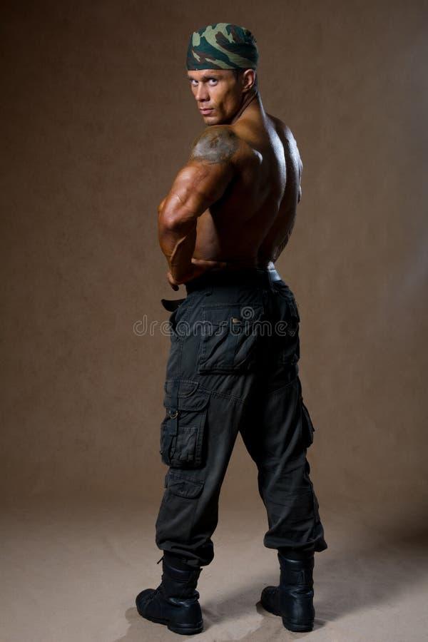 有赤裸躯干的一个肌肉人在充分的成长 库存照片
