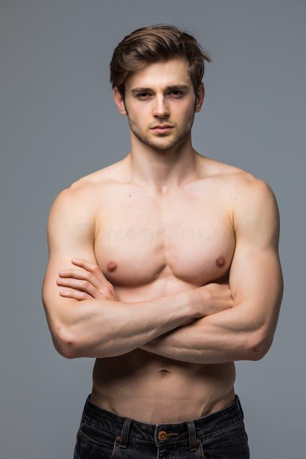 有赤裸躯干的肌肉运动员爱好健美者人在灰色背景 免版税库存照片