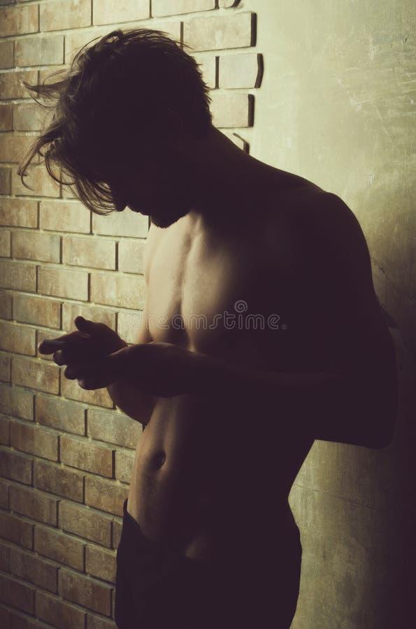 有赤裸躯干的运动员强壮男子在使用手机的树干 免版税库存照片