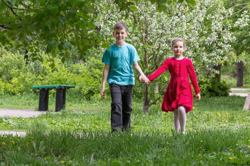 有走在公园的女孩的男孩 免版税库存图片