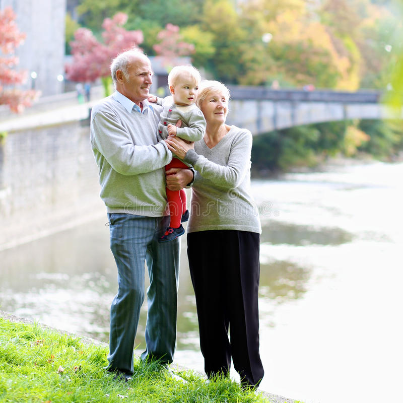 有走在公园的孙女的祖父母 库存照片