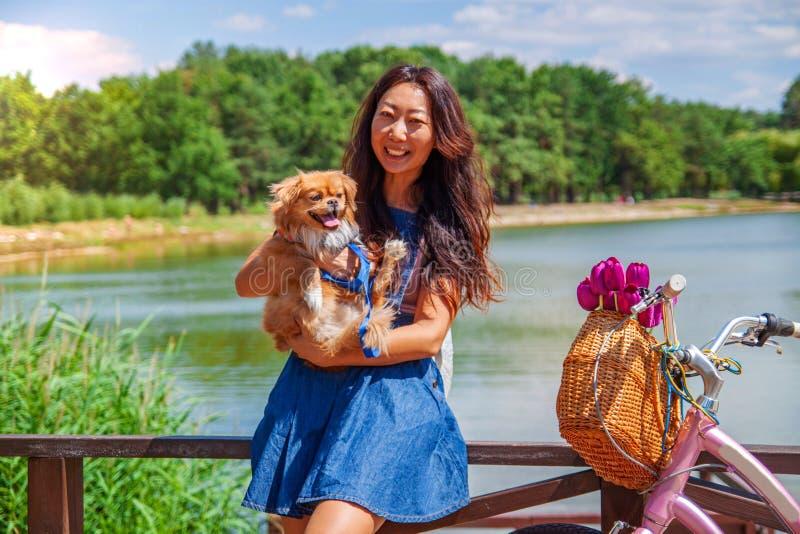 有走在公园的小犬座的逗人喜爱的亚裔女孩 妇女坐与狗的绿草-室外在自然画象 宠物,国内 图库摄影