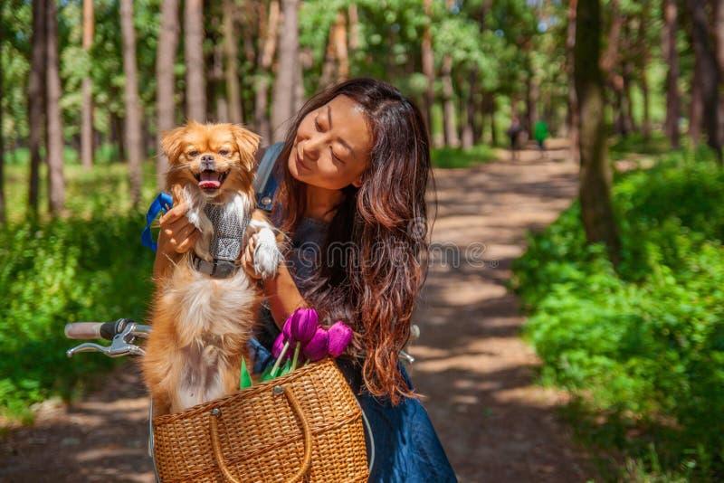 有走在公园的小犬座的逗人喜爱的亚裔女孩 妇女坐与狗的绿草-室外在自然画象 宠物,国内 免版税库存照片