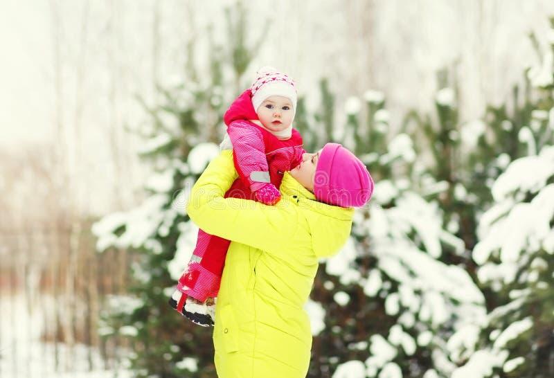 有走在冬日的婴孩的愉快的母亲 免版税库存图片
